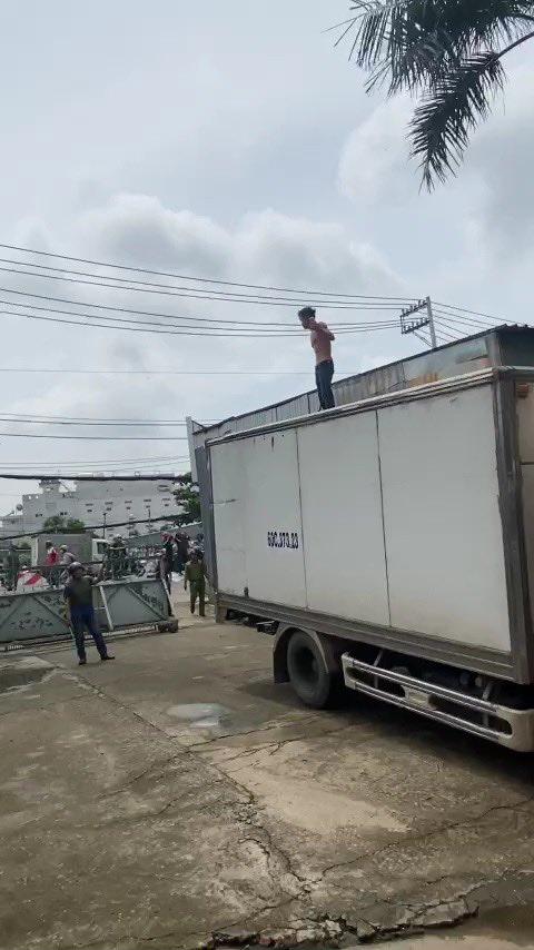 Khống chế người đàn ông ngáo đá lên lên nóc xe tải quậy trên quốc lộ 13 - Ảnh 1.