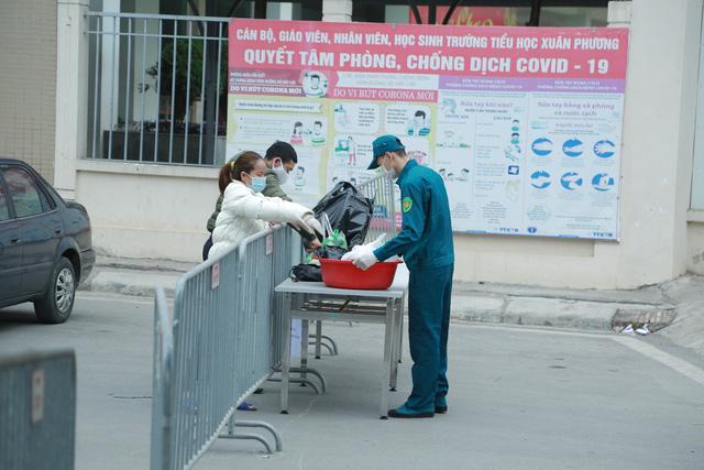 Hàng rào an ninh được bố trí xung quanh Trường tiểu học Xuân Phương, dân quân hỗ trợ chuyển đồ đạc vào trong - Ảnh 1.