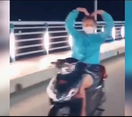 Cô gái không đội mũ bảo hiểm vừa phóng xe vun vút vừa thả tay múa quạt, tạo hình trái tim - Ảnh 2.