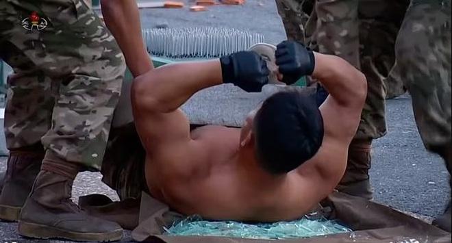 Video binh sĩ Triều Tiên ngực trần nằm trên thuỷ tinh phô diễn sức mạnh - Ảnh 2.