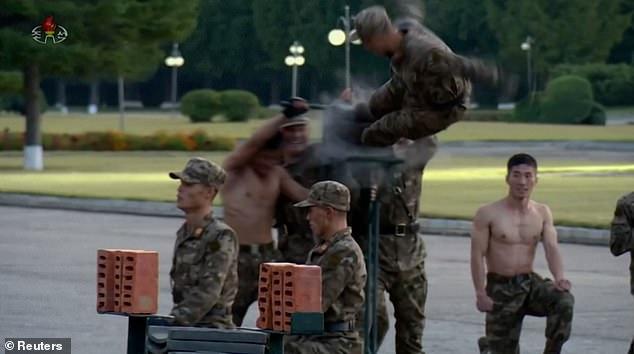 Video binh sĩ Triều Tiên ngực trần nằm trên thuỷ tinh phô diễn sức mạnh - Ảnh 4.