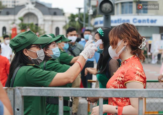 Ảnh: Người Sài Gòn xếp hàng đo thân nhiệt, đeo khẩu trang vào check in đường hoa Nguyễn Huệ - Ảnh 1.