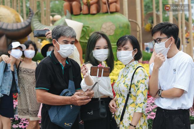 Ảnh: Người Sài Gòn xếp hàng đo thân nhiệt, đeo khẩu trang vào check in đường hoa Nguyễn Huệ - Ảnh 7.