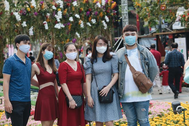 Ảnh: Người Sài Gòn xếp hàng đo thân nhiệt, đeo khẩu trang vào check in đường hoa Nguyễn Huệ - Ảnh 8.