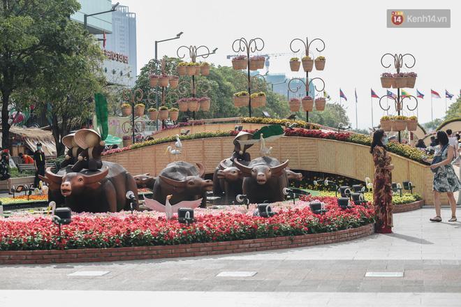 Ảnh: Người Sài Gòn xếp hàng đo thân nhiệt, đeo khẩu trang vào check in đường hoa Nguyễn Huệ - Ảnh 15.