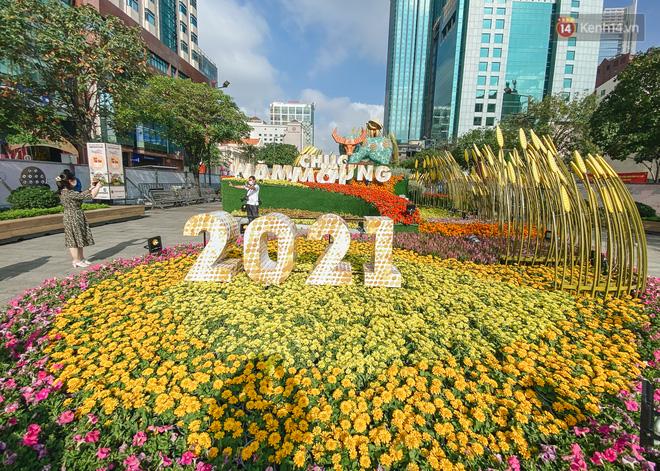 Ảnh: Người Sài Gòn xếp hàng đo thân nhiệt, đeo khẩu trang vào check in đường hoa Nguyễn Huệ - Ảnh 19.