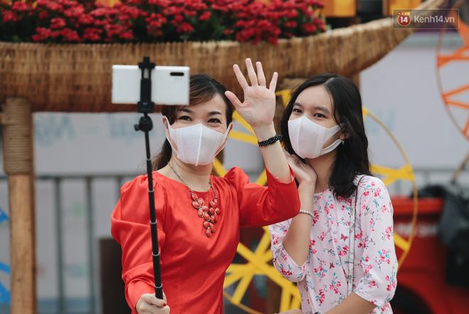 Ảnh: Người Sài Gòn xếp hàng đo thân nhiệt, đeo khẩu trang vào check in đường hoa Nguyễn Huệ - Ảnh 9.