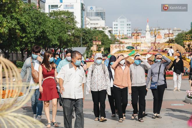 Ảnh: Người Sài Gòn xếp hàng đo thân nhiệt, đeo khẩu trang vào check in đường hoa Nguyễn Huệ - Ảnh 4.