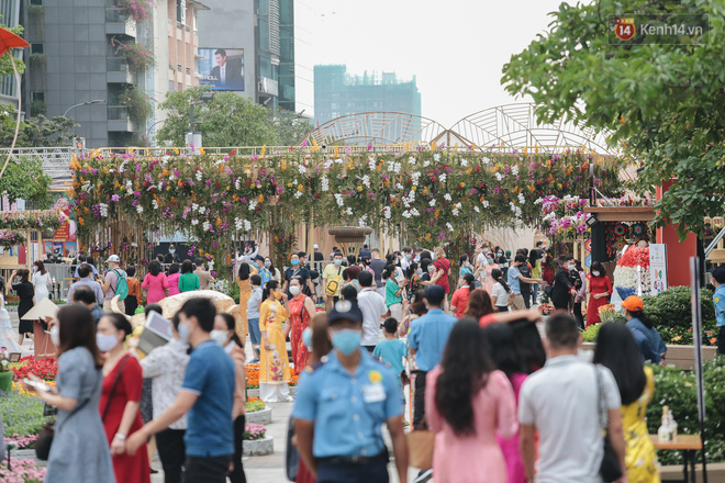 Ảnh: Người Sài Gòn xếp hàng đo thân nhiệt, đeo khẩu trang vào check in đường hoa Nguyễn Huệ - Ảnh 5.
