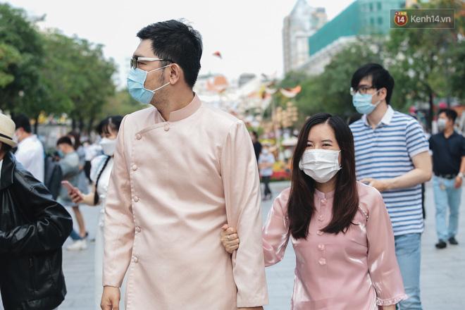 Ảnh: Người Sài Gòn xếp hàng đo thân nhiệt, đeo khẩu trang vào check in đường hoa Nguyễn Huệ - Ảnh 11.