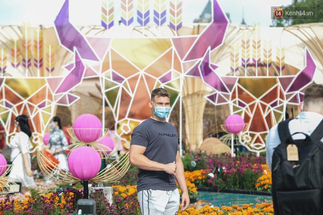 Ảnh: Người Sài Gòn xếp hàng đo thân nhiệt, đeo khẩu trang vào check in đường hoa Nguyễn Huệ - Ảnh 12.