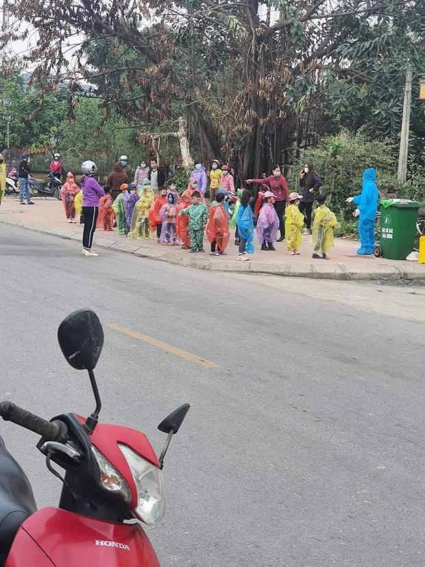 Nhìn hình ảnh các em nhỏ Hải Dương mặc áo mưa, đeo khẩu trang kín mít phòng dịch Covid-19 mà thương! - Ảnh 1.