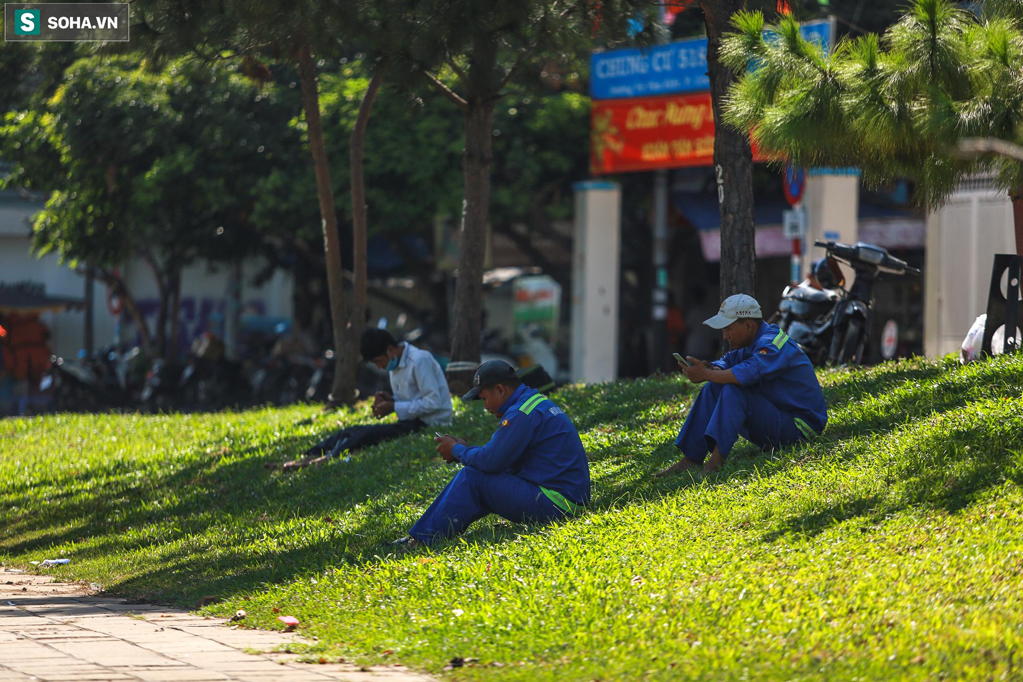 [ẢNH] Đường Sài Gòn nóng như thiêu, người dân vật vã tránh nóng ở góc cây, gầm cầu - Ảnh 6.