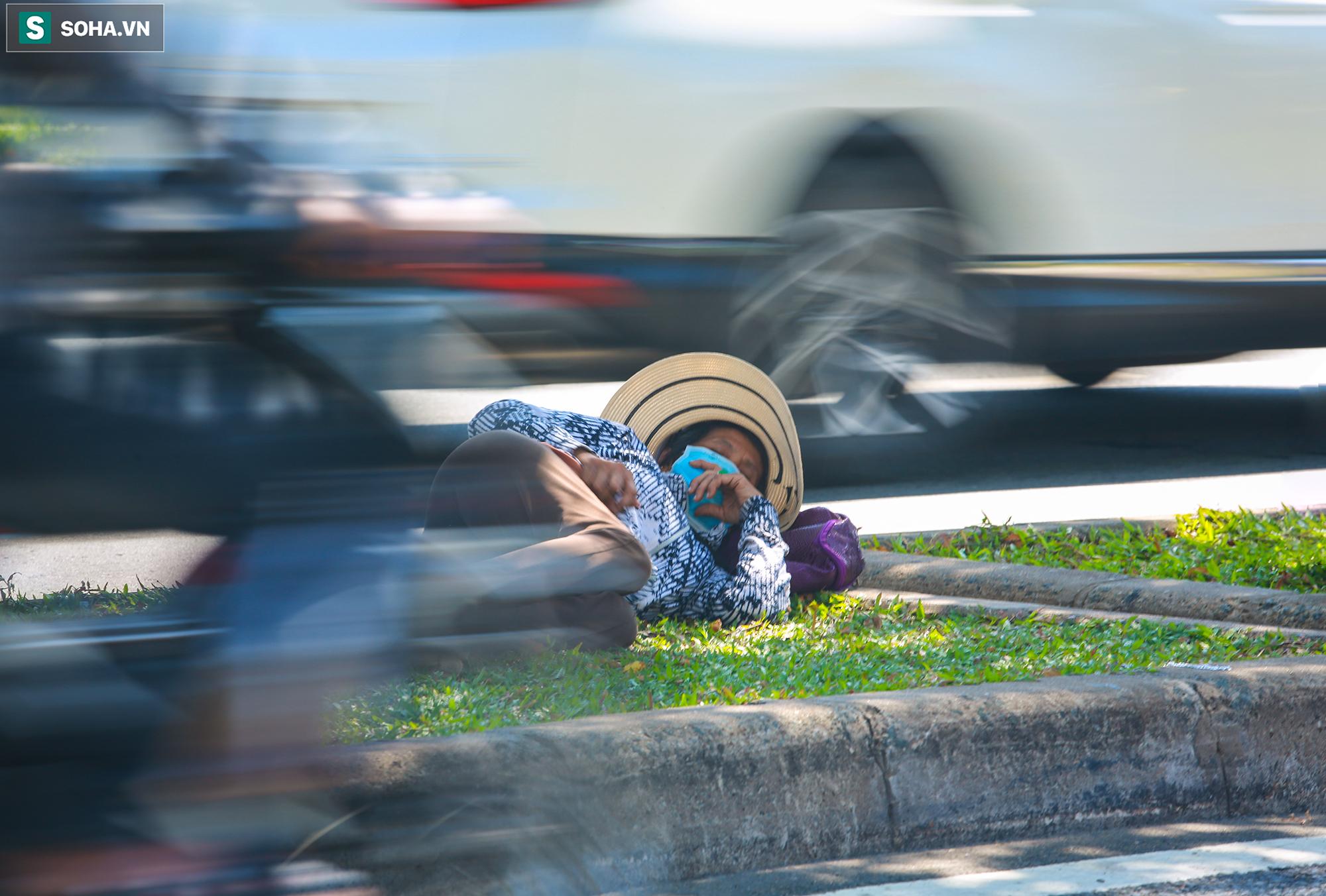 [ẢNH] Đường Sài Gòn nóng như thiêu, người dân vật vã tránh nóng ở góc cây, gầm cầu - Ảnh 11.
