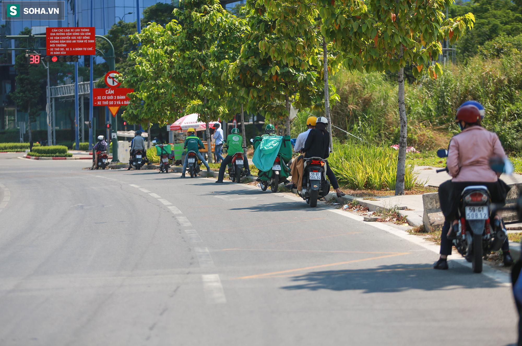 [ẢNH] Đường Sài Gòn nóng như thiêu, người dân vật vã tránh nóng ở góc cây, gầm cầu - Ảnh 9.