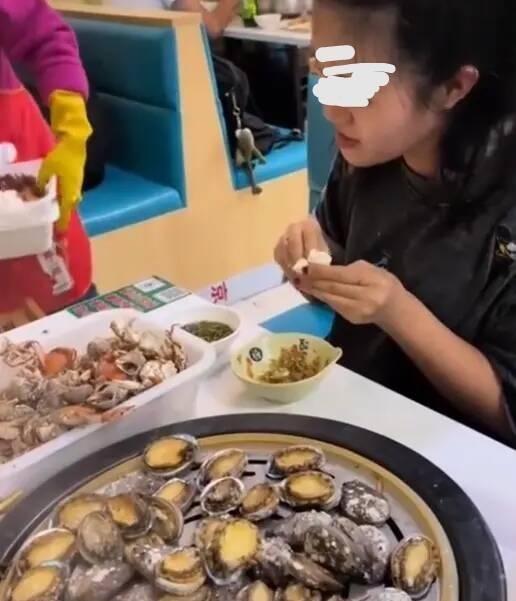 Đi ăn buffet hải sản, cô gái vô tư đánh chén tận 100 con bào ngư, phản ứng khó chịu của ông chủ gây tranh cãi - Ảnh 1.