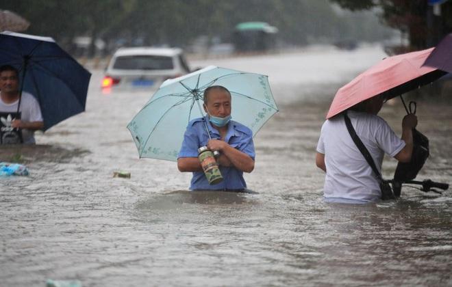 24h qua ảnh: Người dân TQ lội trên đường phố ngập nước lũ - Ảnh 2.