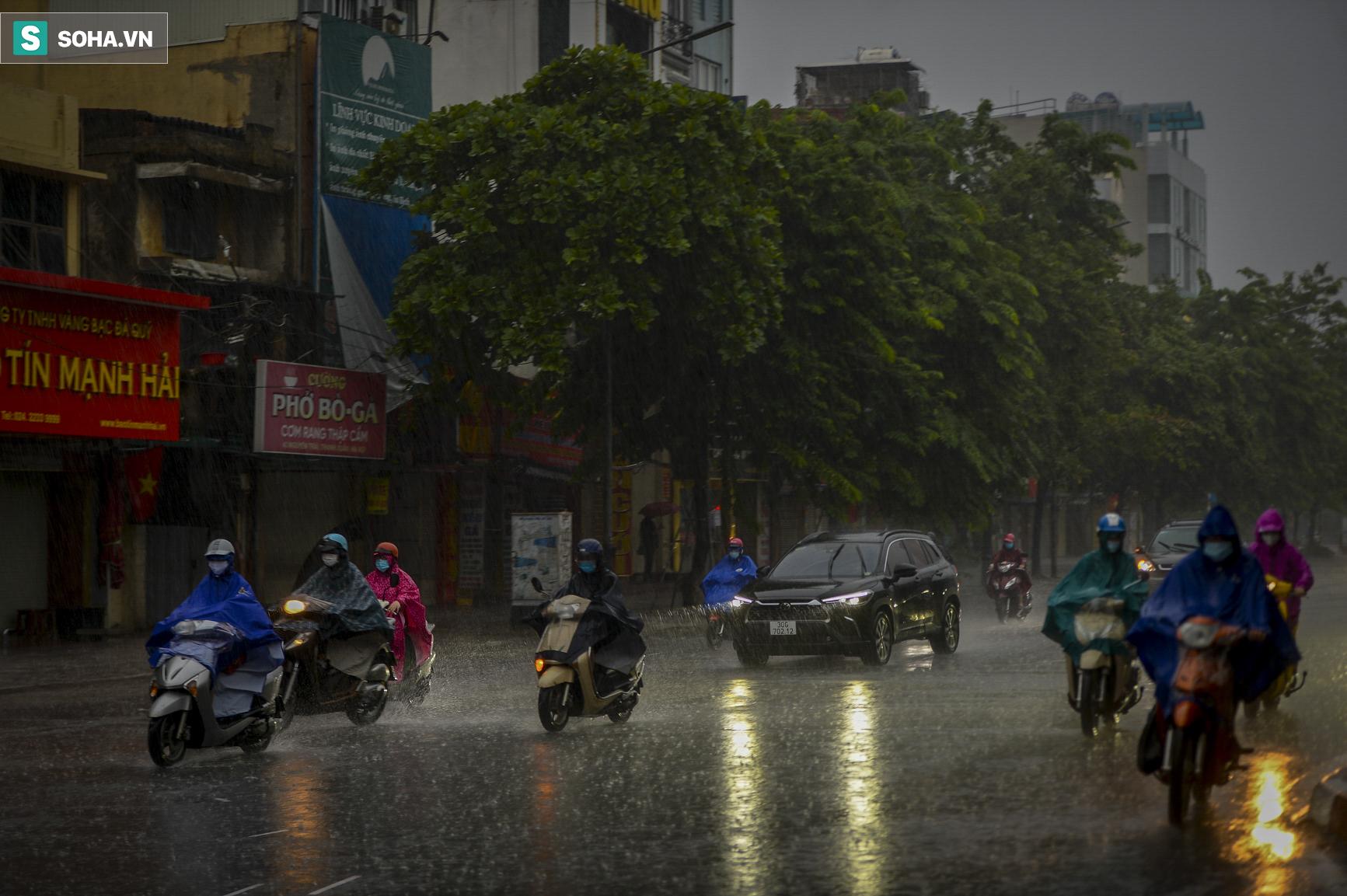Hà Nội: Trận mưa rào lúc 8h sáng khiến trời tối sầm, nhiều phương tiện phải bật đèn để di chuyển - Ảnh 1.