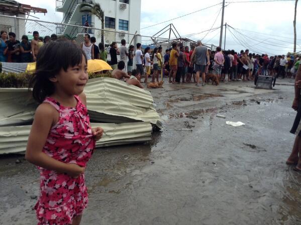Một bé gái đứng khóc vì lạc mẹ trong khi đứng xếp hàng nhận thực phẩm cứu trợ...