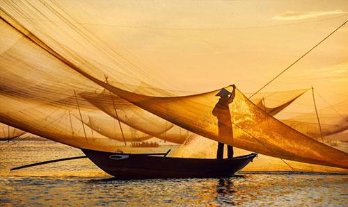 Khi hoàng hôn buông xuống công việc đánh bắt cá vẫn diễn ra.