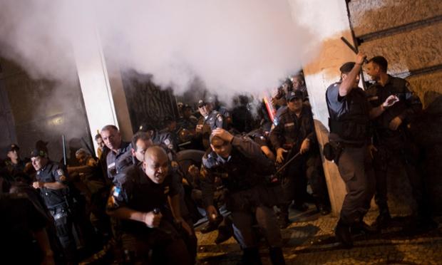 Cảnh sát chống bạo động bắn đạn hơi cay để giải tán người biểu tình xông vào tòa nhà chính quyền thành phố ở Rio de Janeiro, Brazil.