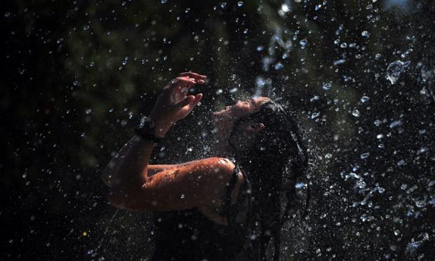 Thiếu nữ tắm mát trong đài phun nước khi nhiệt độ ngoài trời vượt quá 40 độ C ở Seville, Tây Ban Nha.