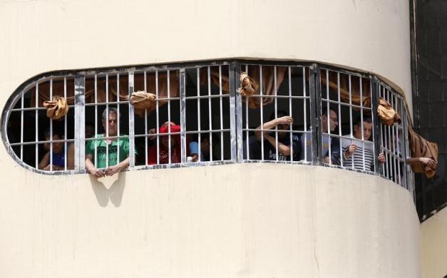 Các phạm nhân nhìn ra ngoài cửa sổ nhà tù Castro-Castro ở Lima, Peru.