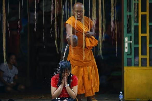 Nhà sư dội nước vào đầu một phụ nữ trong nghi lễ cầu may mắn tại một ngôi chùa ở Phnom Penh, Cam-pu-chia.