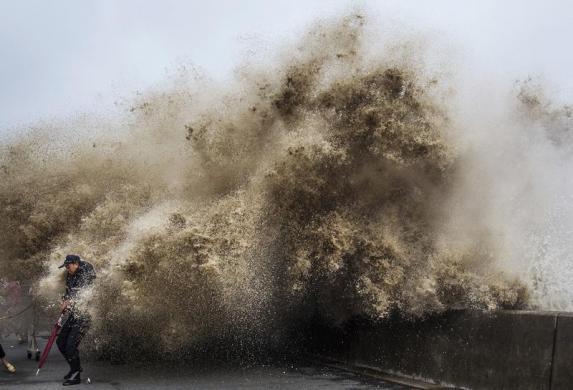 Một người đàn ông cố gắng tránh sóng thủy triều dâng cao do ảnh hưởng của siêu bão Usagi tại thành phố Hàng Châu, tỉnh Chiết, Giang, Trung Quốc.