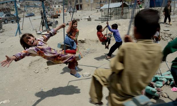 Trẻ em chơi đánh đu gần một nghĩa trang ở Kabul, Afghanistan.