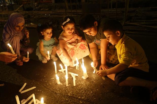 Trẻ em thắp nến cầu nguyện tại hiện trường một vụ đánh bom bằng ô tô ở Beirut, Li Băng.