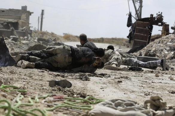 Các chiến binh phiến quân nằm áp sát mặt đất để tránh bị bắn tỉa bởi quân chính phủ ở Aleppo, Syria.