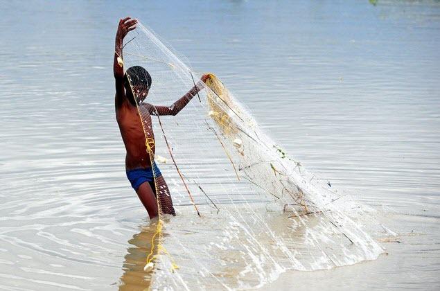 Một cậu bé đánh cá bằng lưới trên sông Hằng ở Uttar Pradesh, Ấn Độ.