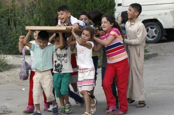 Trẻ em giả vờ mang theo một chiếc quan tài khi chơi trên đường phố ở tỉnh Raqqa, Syria.