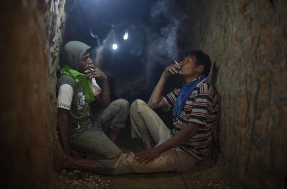 Các công nhân Palestin hút thuốc lá trong khi nghỉ ngơi dưới đường hầm buôn lậu thực phẩm từ Ai Cập tới Dải Gaza.