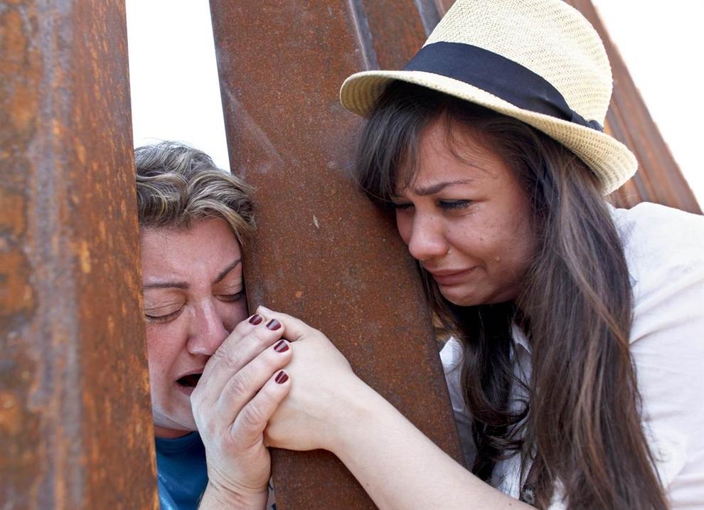 Renata Teodoro, 25 tuổi, nắm tay mẹ, Gorete Borges Teodoro, người bị trục xuất cách đây sáu năm khỏi đất nước Mỹ, qua những chấn song của một hàng rào biên giới Nogales, Ariz