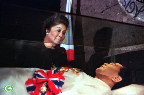 Cựu đệ nhất phu nhân Philippines Imelda Marcos đứng bên thi thể của chồng là cựu Tổng thống Philippines Ferdinand Marcos nằm trong quan tài kính tại lăng Marcos năm 1996. Ông Marcos qua đời khi sống lưu vong ở Hawaii (Mỹ) vào năm 1986. Bà Imelda Marcos đã ướp xác chồng và chuyển thi thể của ông về nước vào năm 1993.