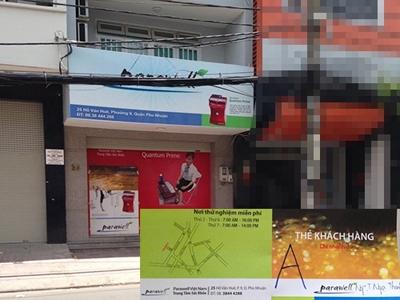 Cánh cửa căn nhà số 25 đóng kín bằng tấm pa nô quảng cáo thật to các sản phẩm của Công ty Parawell (ảnh lớn)             và tấm thẻ thành viên khách hàng mà nhân viên Công ty Parawell cấp cho phóng viên (ảnh nhỏ)             Bệnh nan y: Dùng máy là khỏi (!?)