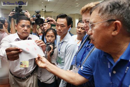 Trưởng đoàn quan sát của Indonesia Muhammad Jusuf Kalla (phải) kiểm tra tem bảo chứng