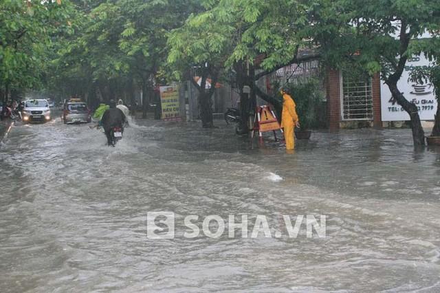 Đối diện đường Vạn Phúc (Ba Đình, Hà Nội), các xe cũng đang vất vả để vượt qua cung đường ngập lụt dưới ánh nhìn của nhân viên công ty cấp thoát nước.