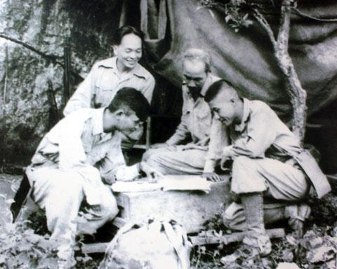 Chủ tịch Hồ Chí Minh, đại tướng Võ Nguyên Giáp cùng trung đoàn trưởng Thái Dũng và tiểu đoàn trưởng Dũng Mã đang nghiên cứu sơ đồ tác chiến trong chiến dịch Biên Giới 1950.