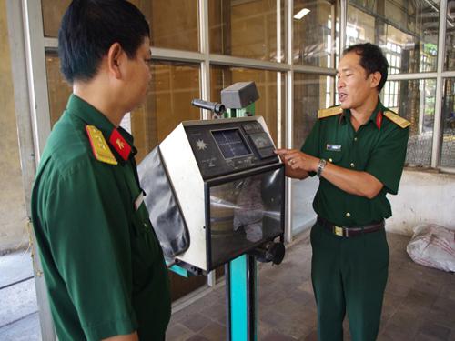Thiếu tá Vũ Nam Hải - Kiểm tra viên Phòng KSC Nhà máy Z151 giới thiệu về thiết bị kiểm tra độ sáng của đèn pha xe sau sửa chữa. Đèn pha sẽ được rọi vào bề mặt của thiết bị để đo độ sáng.