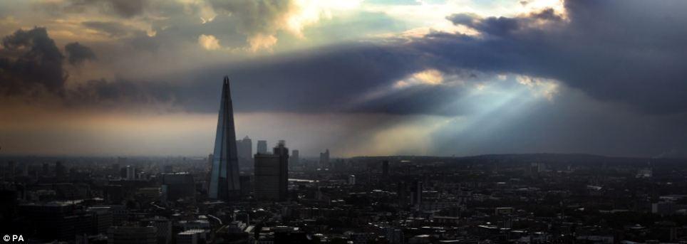 Ấn tượng: Các phía đông nam của nước Anh dự kiến sẽ có mưa và gió liên tục vào cuối tuần.  Ảnh là mặt trời mọc đằng sau The Shard như nhìn thấy từ London Eye