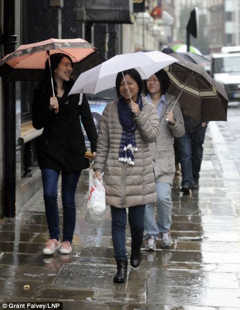 Người mua sắm ở London để ráo dưới ô dù