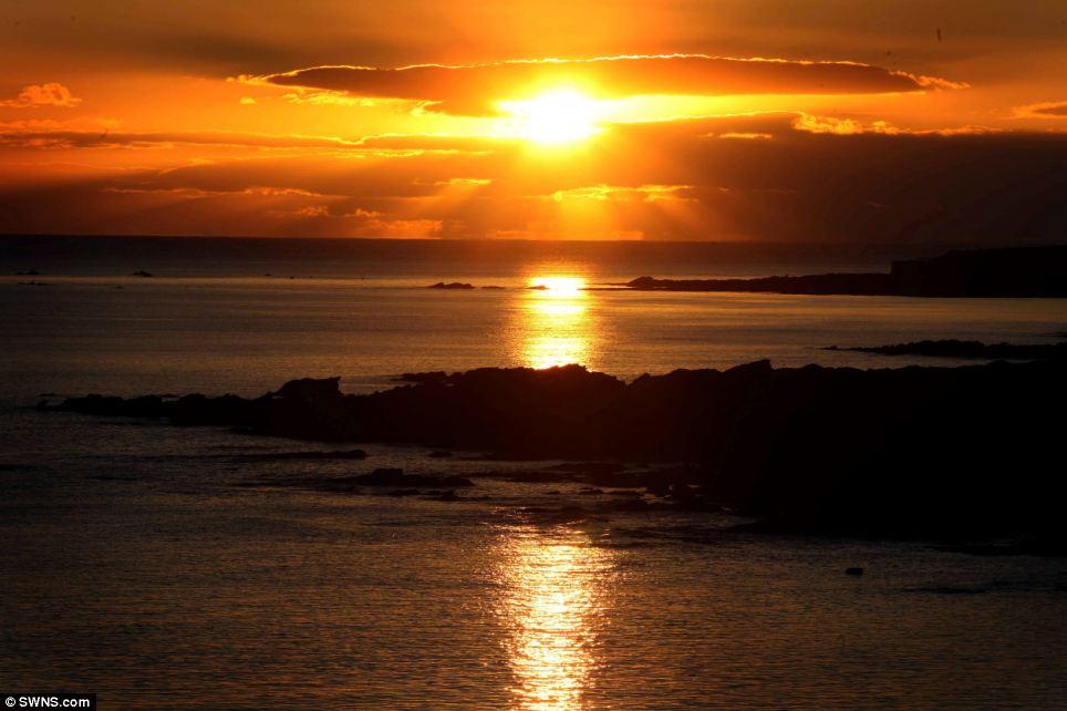 Thiết lập bình tĩnh: Mặt trời xuất hiện trên đường chân trời tại Wembury bãi biển ở Devon sáng nay