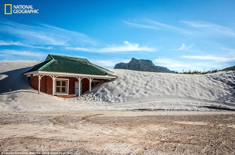 Nuốt Cát: Bức ảnh này được chụp ở Cape Town Nam Phi.  Một ngôi nhà bị nuốt chửng bởi cảnh quan thay đổi