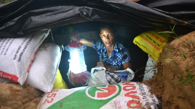 Rất nhiều người dân miền Trung đã phải đào hầm tránh bão. Trong ảnh: Bà Trương Thị Chín (45 tuổi, xã Duy Hải, Quảng Nam) thắp đèn sạc ở dưới hầm trú bão - Ảnh: Lê Trung