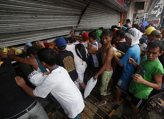 Thiếu thốn mọi thứ, người dân tại Tacloban Philippines xô cửa của một hiệu tạp hoá nhằm lấy đi bất cứ thứ gì có thể. Tình trạng hôi của, cướp bóc đang diễn ra trên khắp những nơi bị siêu bão Haiyan quét qua.