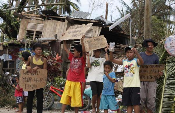 Trẻ em cầm biển yêu cầu được hộ trợ thực phẩm và giúp đỡ dọc một con đường ở thị trấn Tabogon.