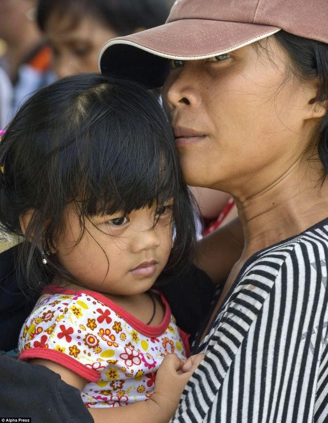 Bé gái cùng mẹ chờ lên máy bay để đi sơ tán.